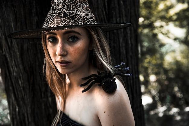 Mujer atractiva con sombrero y araña artificial en el hombro