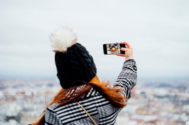 Mujer atractiva con sombrero negro tomando un selfie