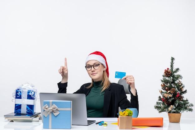 Mujer atractiva con sombrero de santa claus y gafas sentado en una mesa de regalo de navidad y sosteniendo una tarjeta bancaria apuntando hacia arriba en la oficina