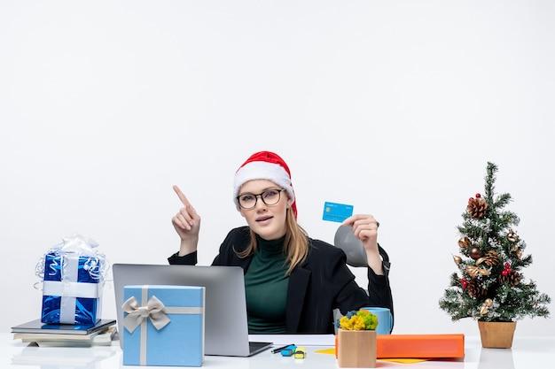 Mujer atractiva con sombrero de santa claus y gafas sentado en una mesa de regalo de navidad y sosteniendo una tarjeta bancaria mirando arriba en la oficina
