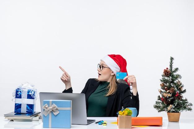 Mujer atractiva con sombrero de santa claus y gafas sentado en una mesa de regalo de navidad y sosteniendo una tarjeta bancaria en la oficina
