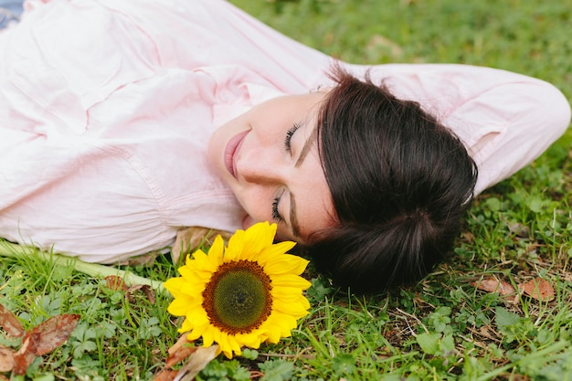 Mujer atractiva soñando y tumbado en la hierba