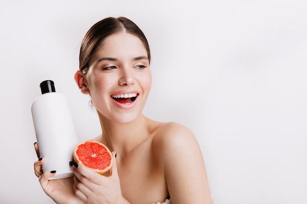 Mujer atractiva sonriendo afablemente en la pared blanca. chica sin maquillaje demuestra champú de uva y cabello.