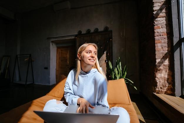 Mujer atractiva sonriente que miente en cama usando la computadora portátil