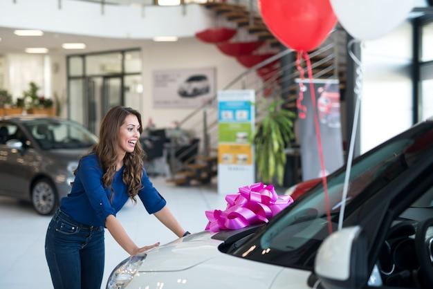 Mujer atractiva sorprendida con un coche nuevo en el concesionario de vehículos