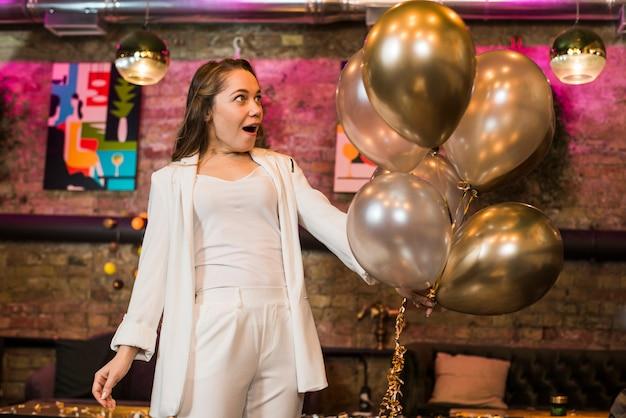 Mujer atractiva sorprendida mirando globos de plata en bar