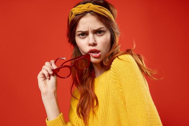 Mujer atractiva suéter amarillo ropa de moda estilo callejero fondo rojo. foto de alta calidad