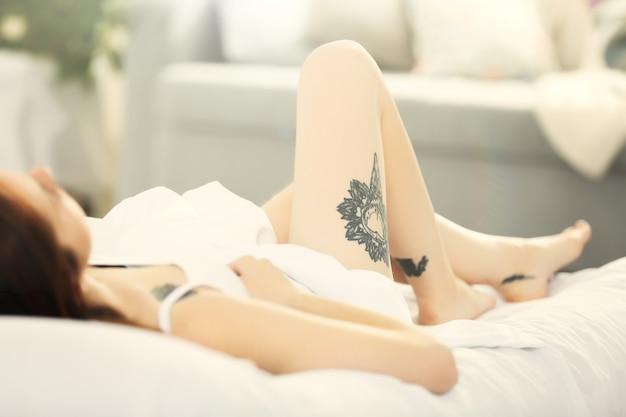 Mujer atractiva con tatuaje acostado en la cama