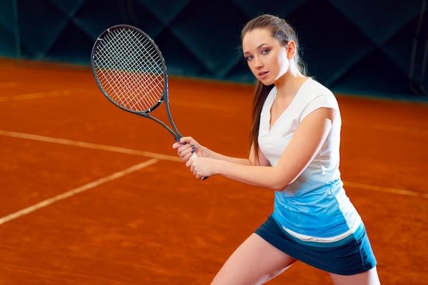 Mujer atractiva tenista esperando servicio en la cancha cubierta