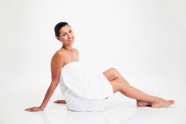 Mujer atractiva en toalla sentada en el suelo