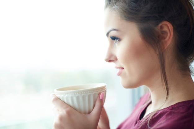 Mujer atractiva tomando café por la mañana