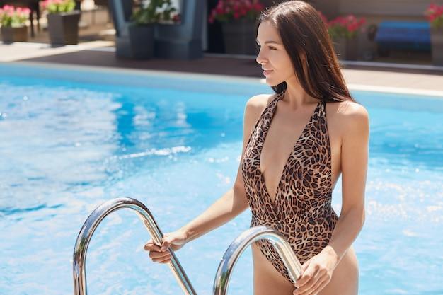 Mujer atractiva en traje de baño de leopardo saliendo de la piscina y mirando a un lado, chica de cabello oscuro descansando en el resort, relajándose en la piscina