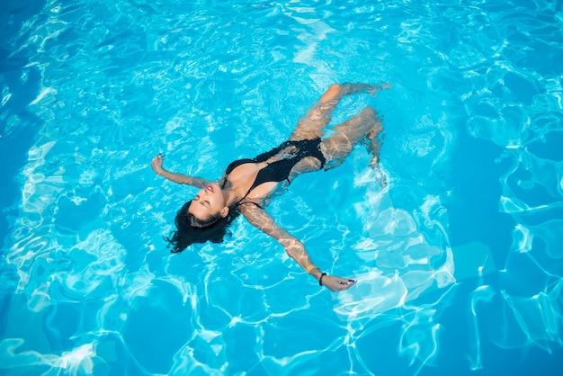 Mujer atractiva en un traje de baño negro que flota sobre su espalda en la piscina y se relaja