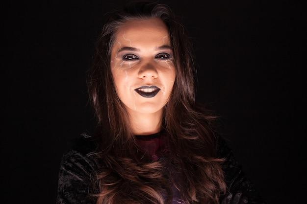 Mujer atractiva con un traje de bruja para halloween mirando a la cámara sobre fondo negro.