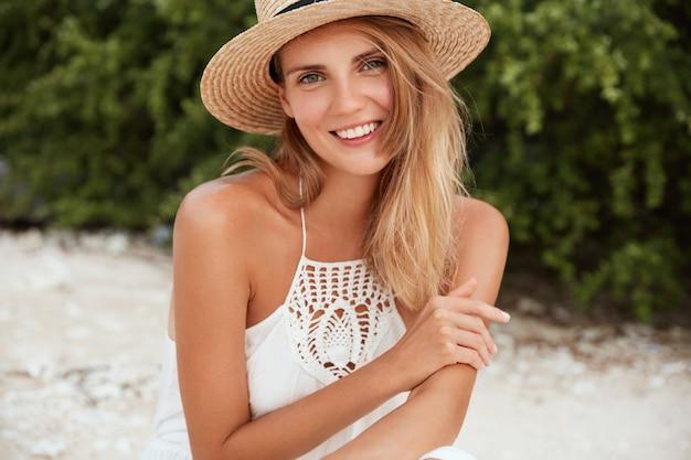 Mujer atractiva usa sombrero de paja de verano y vestido blanco, posa en la playa de arena, tiene una amplia sonrisa en la cara, disfruta del tiempo de recreación en un país tropical, posa al aire libre personas y tiempo de recreación