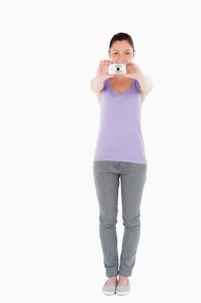 Mujer atractiva usando una cámara mientras está de pie