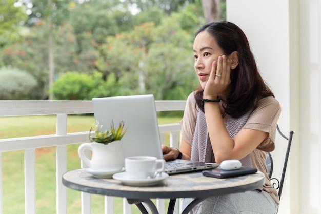 Mujer atractiva usando laptop y mirando a otro lado.