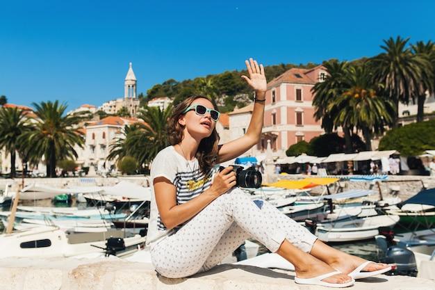 Mujer atractiva de vacaciones en europa junto al mar en un crucero tomando fotografías con la cámara