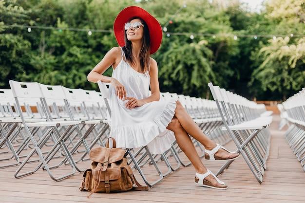 Mujer atractiva vestida con vestido blanco, sombrero rojo, gafas de sol sentado en el teatro al aire libre de verano en una silla sola, tendencia de moda de estilo callejero de primavera, accesorios, viajar con mochila