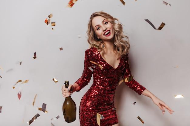 Mujer atractiva en vestido de fiesta posando con sonrisa