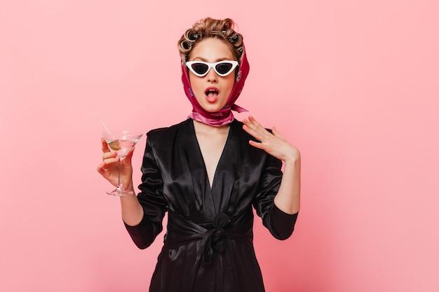 Mujer atractiva en vestido negro y pañuelo en la cabeza posando en la pared rosa con copa de martini