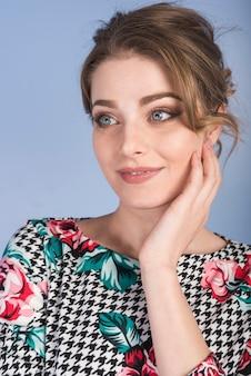 Mujer atractiva en vestido sosteniendo la mejilla