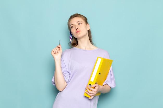 Una mujer atractiva de vista frontal en camisa-vestido azul con archivos amarillos sobre fondo azul trabajo de negocios de ropa de dama