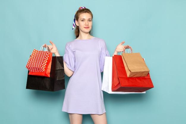 Una mujer atractiva de vista frontal en camisa-vestido azul sosteniendo paquetes de compras en azul
