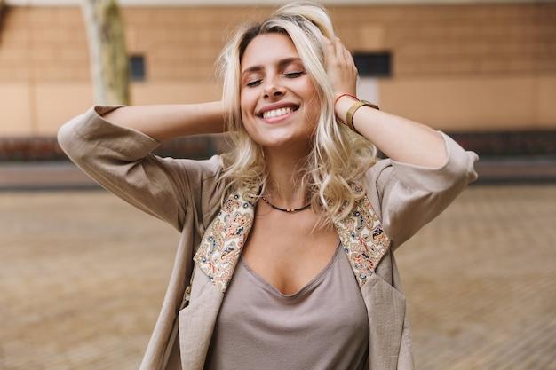 Mujer atractiva vistiendo ropa elegante sonriendo y agarrando la cabeza, mientras camina por las calles de la ciudad