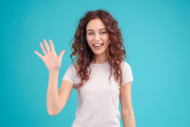 Mujer atractiva wawing hola y mostrando la palma de la mano aislada sobre fondo azul turquesa