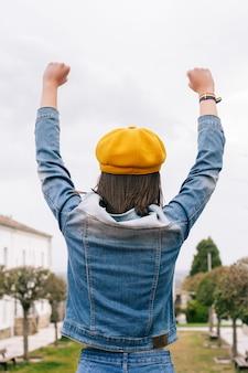Mujer de atrás con las manos arriba y pulsera lgbt, foto vertical