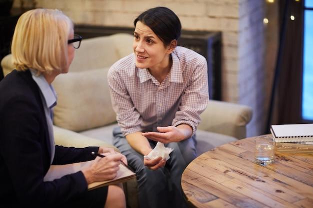 Mujer atribulada hablando con psicólogo