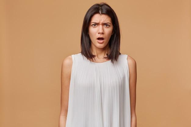 Mujer aturdida en vestido blanco de pie con la boca abierta y mirando, se siente ofendida injustamente privada
