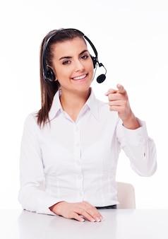 Mujer con auriculares apuntando hacia ti