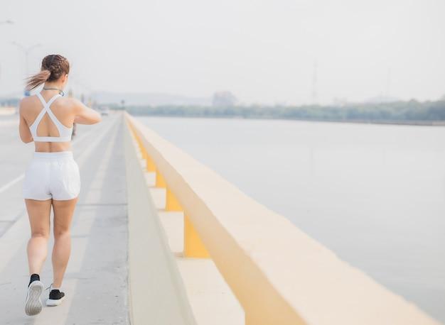 Mujer con auriculares corredores trotar cardio correr entrenamiento de resistencia tiro en cámara lenta de piernas zapatillas de deporte corredor piernas correr en la calle