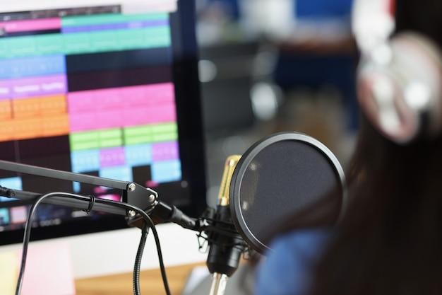 Mujer en auriculares delante de micrófono mira monitor con locutor de radio de pista de sonido