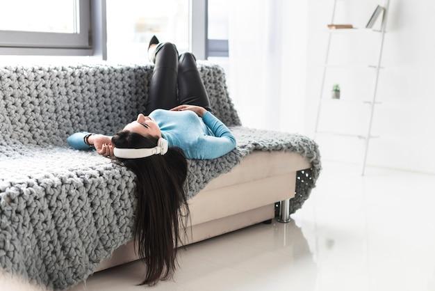 Mujer en auriculares descansando en el sofá