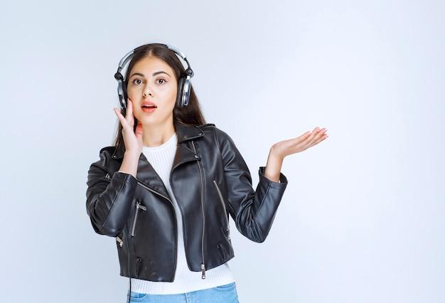 Mujer con auriculares escuchando música y bailando.