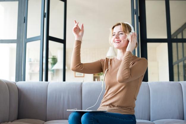 Mujer en auriculares escuchando música y bailando.