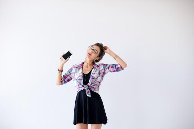 Mujer con auriculares y gafas escuchando música y bailando