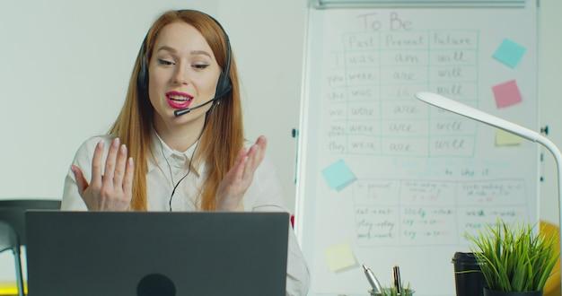 Mujer en auriculares hablando con estudiantes a través de videoconferencia en clase vacía.