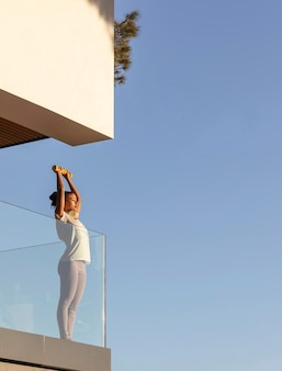 Mujer con auriculares haciendo fitness en casa