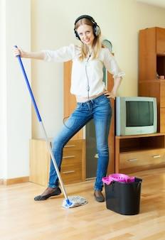 Mujer en auriculares lavar piso en la sala de estar