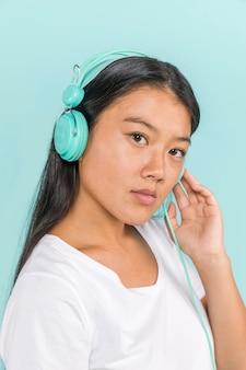 Mujer con auriculares y mirando a cámara