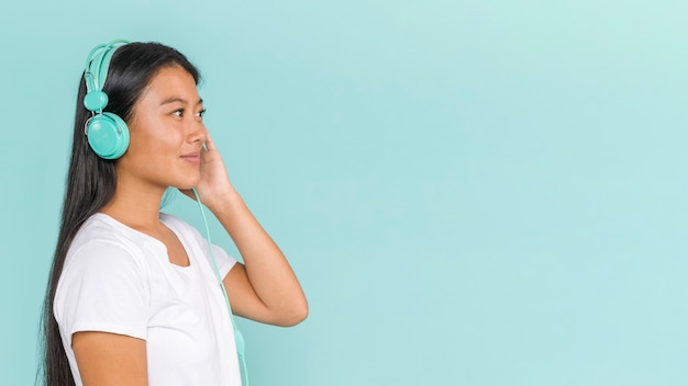 Mujer con auriculares y mirando a otro lado