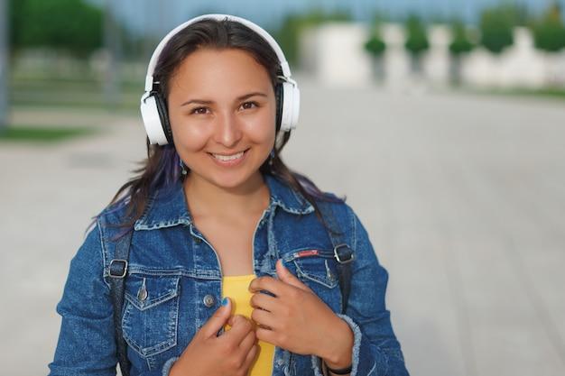 Mujer en auriculares. mujer joven emocional en auriculares escuchando música al aire libre en una hierba verde.