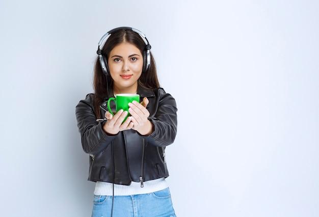 Mujer con auriculares ofreciendo una taza de bebida verde a alguien.