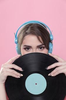 Mujer con auriculares posando con disco de vinilo