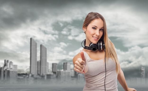 Mujer con auriculares y un pulgar levantado