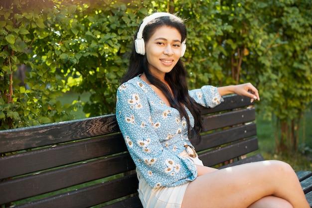 Mujer con auriculares sentado y mirándonos